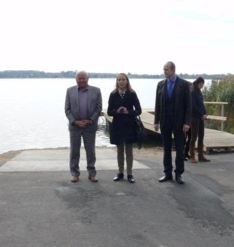 Na tle jeziora widać urzędnikó - kobiete i mężczyznę któzy sa dumni ze swoich osiągnięć